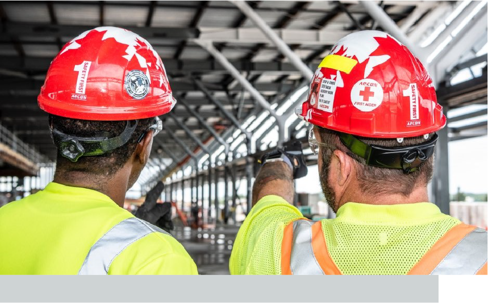 Two men wearing safety gear observing a construction site