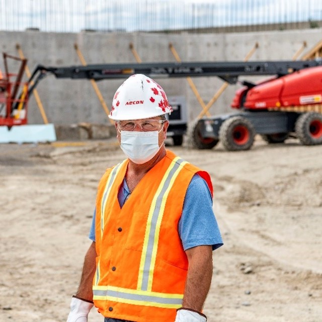Man wearing a hard hat and a surgical mask on a construction site.